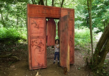 A young trail visitor enters the iconic wardrobe entrance to 'Narnia'